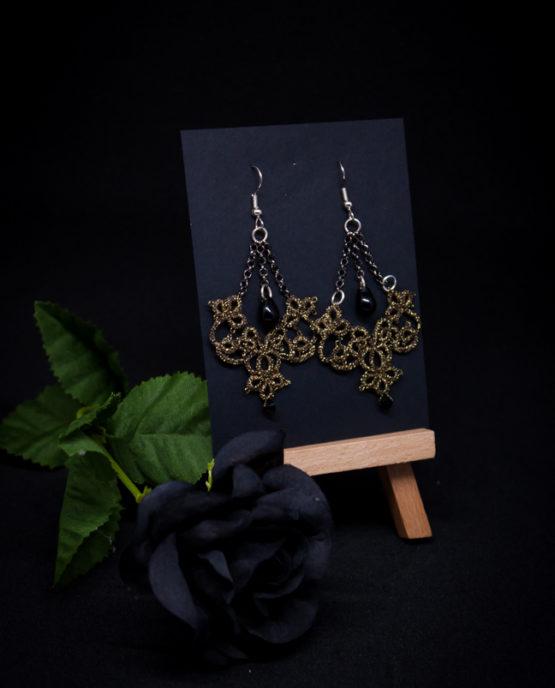 Boucles d'oreilles en dentelle dorée avec perle noire suspendue.