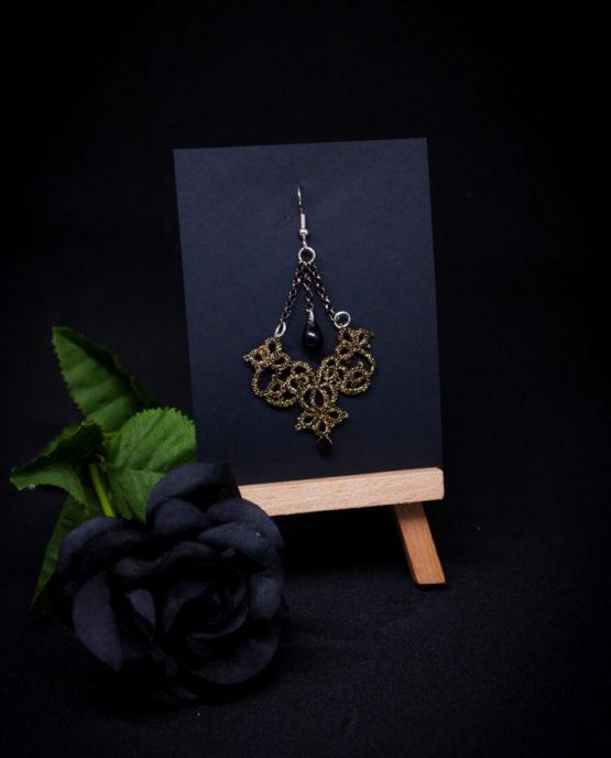 Boucle d'oreille en dentelle dorée avec perle noire suspendue.