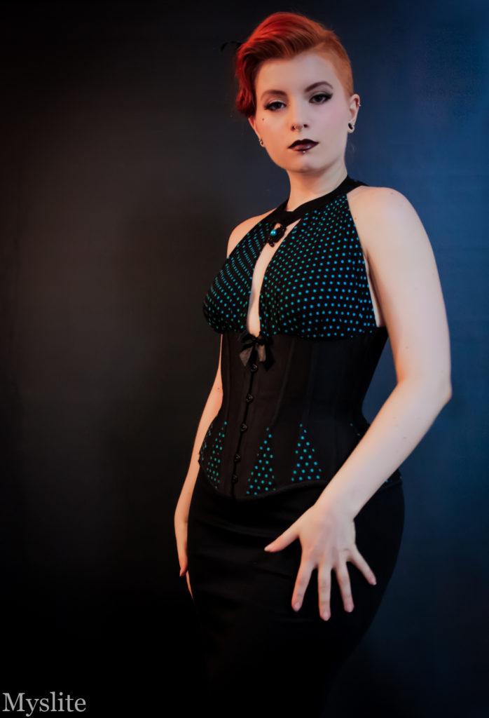 Un corset underbust noir, avec des goussets à pois bleus aux hanches et deux pièces de tissu froncés qui viennent recouvrir la poitrine et créent un joli dos-nu.