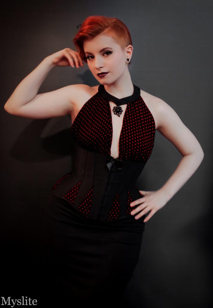 Un corset underbust noir, avec des goussets à pois rouges aux hanches et deux pièces de tissu froncés qui viennent recouvrir la poitrine et créent un joli dos-nu.