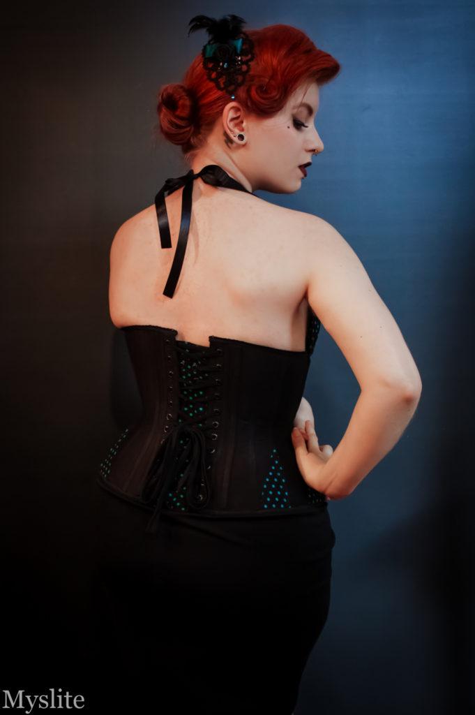 Vue de dos du corset noir à goussets bleus, avec un panneau de modestie à pois bleus, assorti aux goussets.